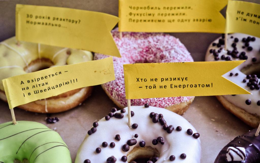 """Перед засіданням Колегії активіст у костюмі Діда Симона зі Спрінгфільда роздавав людям, що прямували на Колегію, пончики із саркастичними написами: """"Не думай про завтра – з'їж пончик"""", """"Чорнобиль пережили, Фукусіму пережили, переживемо ще одну аварію"""", """"Хто не ризикує –той Енергоатом""""."""